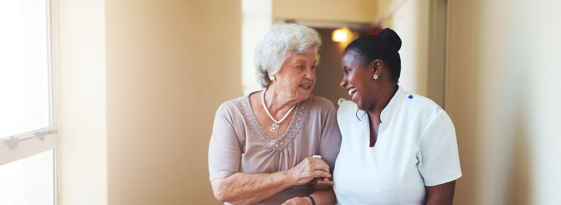 a senior woman and a caregiver smiling at each other