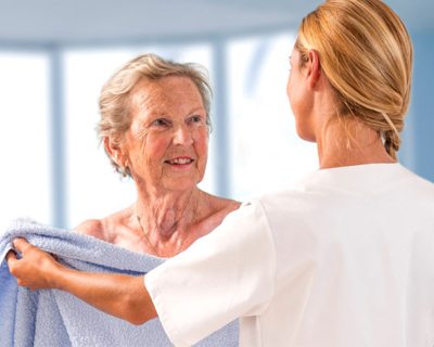a caregiver assisting a senior woman in the shower