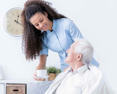 a caregiver serving coffee to a senior man