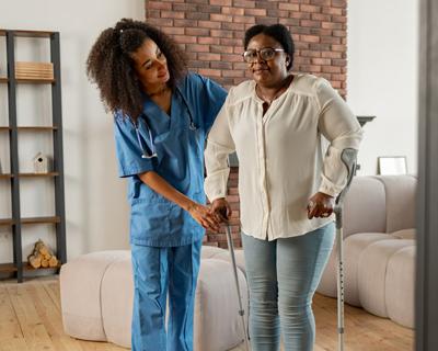 a nurse assisting a senior woman walk