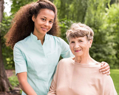 a caregiver and a senior woman taking a walk outside