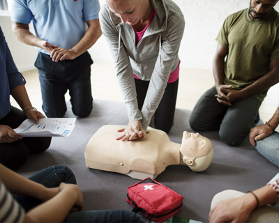 a group of people watching a CPR demonstration