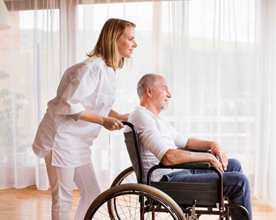 a caregiver and a senior man looking out the window