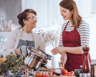 an occupational therapist assisting a senior woman prepare a meal